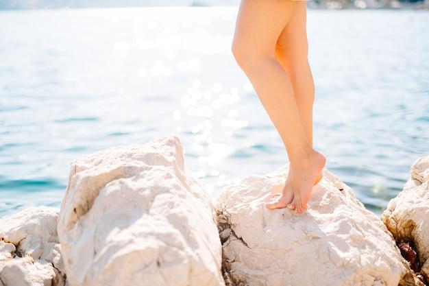 Pernas de uma mulher em pé sobre uma pedra perto da água em uma praia rochosa