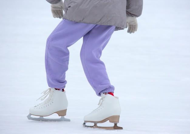 Pernas de uma mulher patinando no gelo em uma pista de gelo. hobbies e lazer
