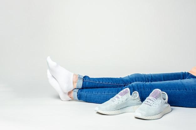 Pernas de uma mulher sentada no chão sobre um fundo claro com tênis