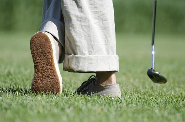 Pernas de uma pessoa jogando golfe na paisagem verde