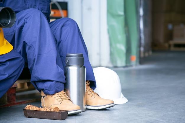 Pernas de uma trabalhadora de fábrica sentada no chão perto de uma garrafa térmica e biscoitos