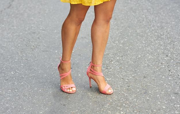 Pernas de verão de uma jovem com um lindo bronzeado em sandálias de salto