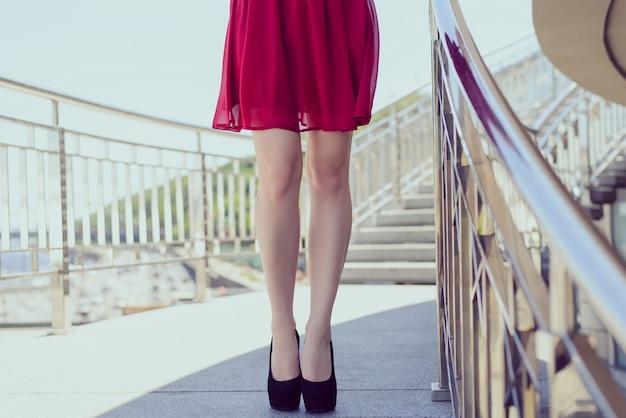 Pernas de wmans em salto alto e vestido vermelho na escada