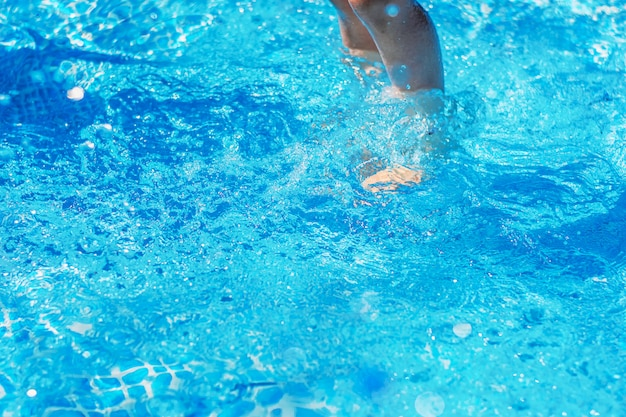 Pernas debaixo d'água na piscina azul closeup