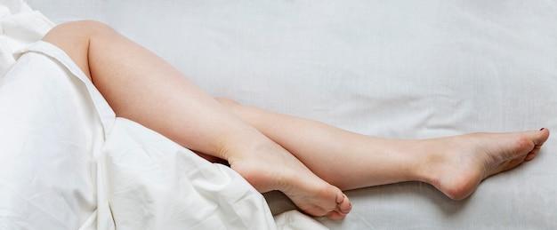 Pernas delgadas de uma mulher dormindo na cama. sono completo e relaxamento.