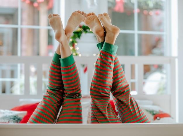 Pernas descalças do homem e da mulher, de pijama de natal vermelho e verde, despidas no quarto branco.