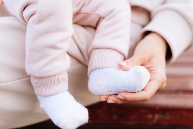 Pernas do bebê e mãos da mãe fechadas