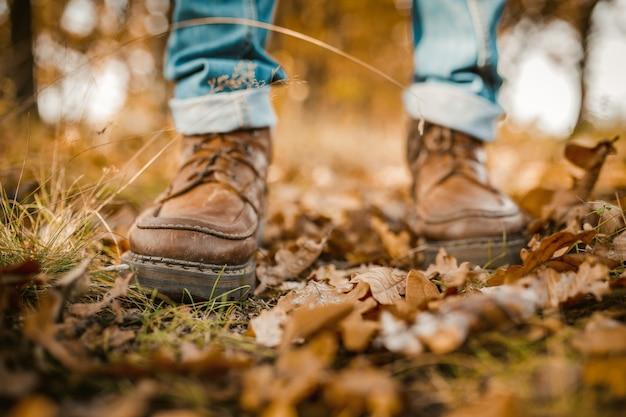 Pernas do homem andando nas folhas de outono