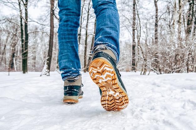 Pernas do homem em botas andando na neve