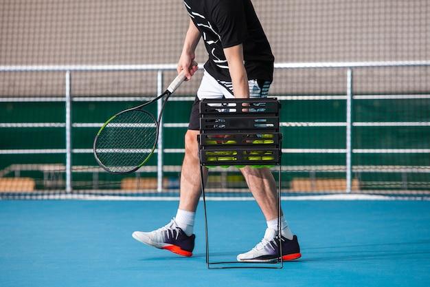 Pernas do homem em uma quadra de tênis fechada com bola e raquete