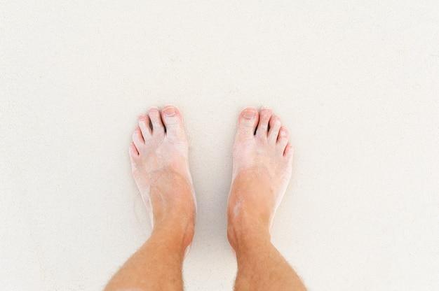 Pernas do homem na areia branca do oceano índico