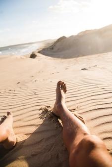 Pernas do homem na areia close-up