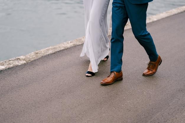 Pernas do noivo de calça azul e a noiva de vestido branco caminham pela estrada de asfalto