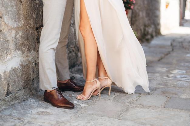 Pernas do noivo e da noiva se abraçando perto do muro de pedra na rua estreita do velho gorol