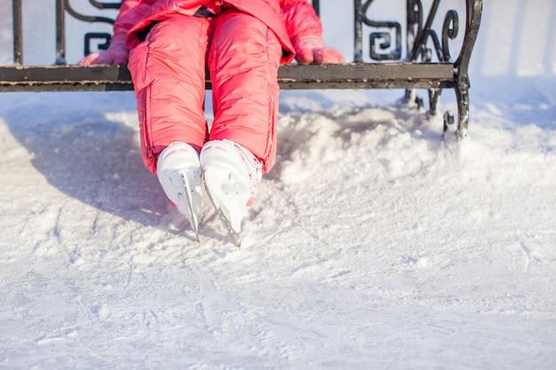 Pernas do pequeno patinador de pé na pista de gelo do inverno