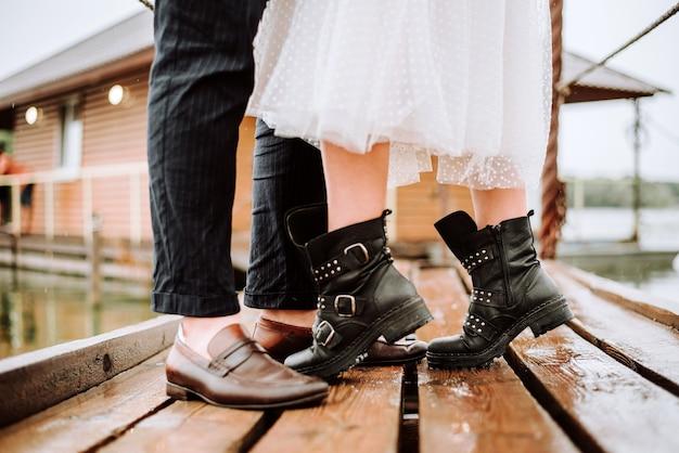 Pernas do recém-casado no fundo do cais. a noiva e o noivo levantam e posam de botas no cais.
