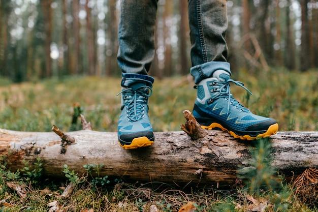 Pernas dos homens em botas de trekking para atividade ao ar livre na árvore caída