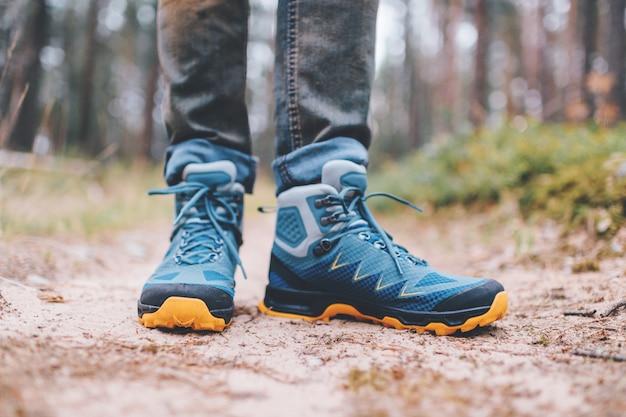 Pernas dos homens em botas de trekking para atividade ao ar livre na estrada da floresta
