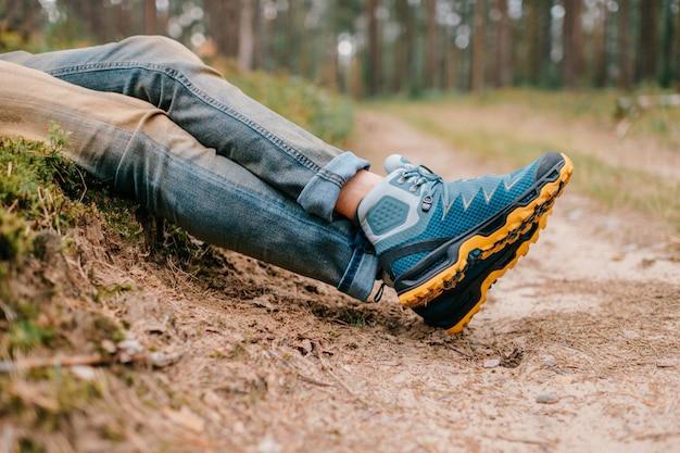 Pernas dos homens em botas de trekking para atividades ao ar livre.