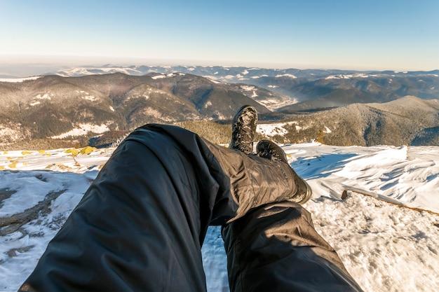 Pernas dos homens em sapatos de inverno contra panorama sobre as montanhas dos cárpatos.