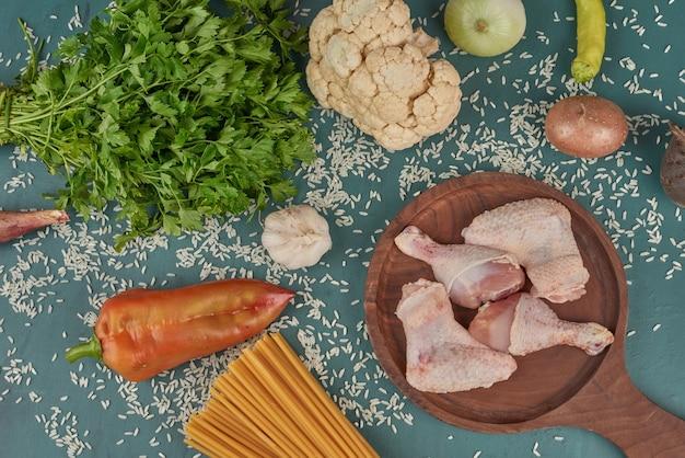 Pernas e asas de frango cru em uma placa de madeira com macarrão e ervas.
