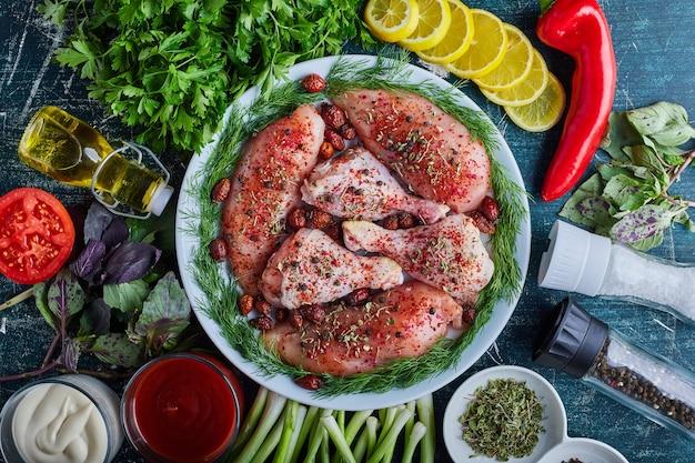 Pernas e filé de frango cru em um prato verde.