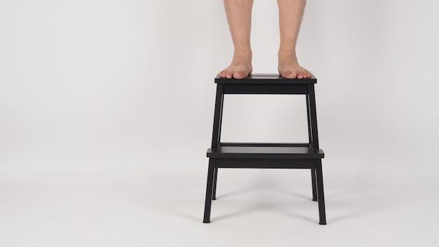 Pernas e pés descalços ficam no banquinho ou escadas de madeira no fundo branco.