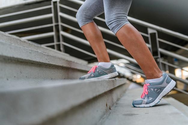 Pernas e sapatos de um corredor correndo até uma escadaria