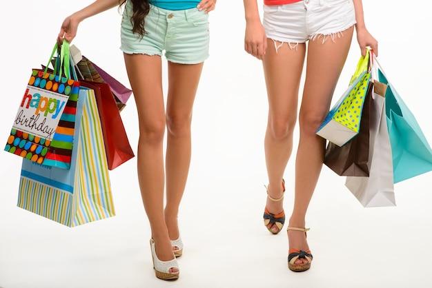 Pernas elegantes de meninas andando com sacolas de compras.