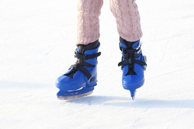 Pernas em azul patinando na pista de gelo