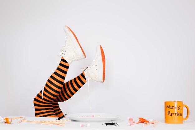 Pernas em meias listradas e sapatos de lona