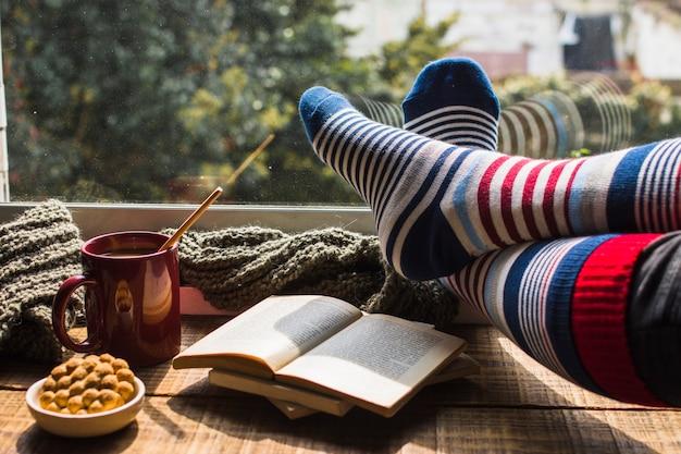 Pernas em meias listradas perto da janela