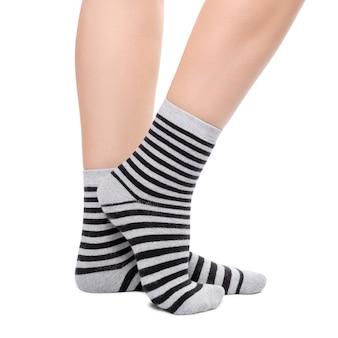 Pernas em meias listradas quentes pretas e cinza isoladas no branco