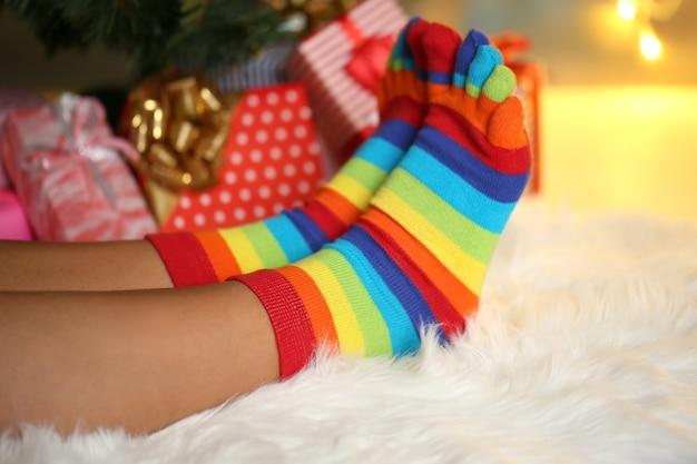Pernas em meias perto da árvore de natal na carped