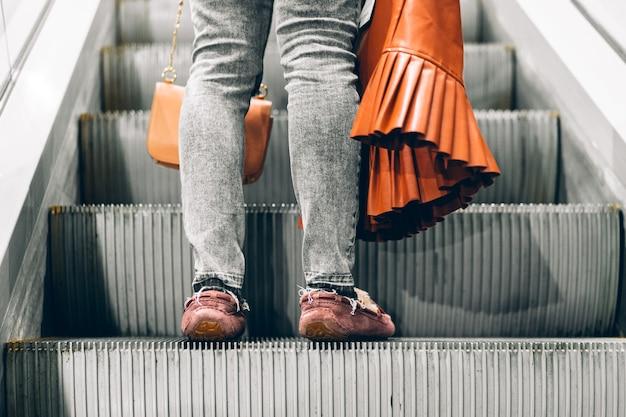 Pernas em pé na escada rolante de um shopping
