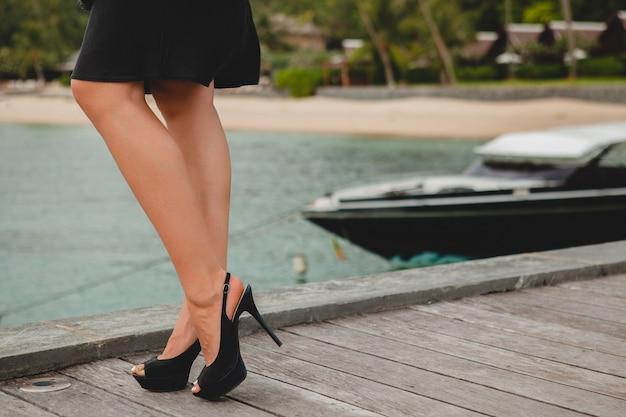 Pernas em sapatos pretos de salto alto de mulher sexy e atraente de luxo vestida de vestido preto posando no cais em hotel resort de luxo, férias de verão, praia tropical