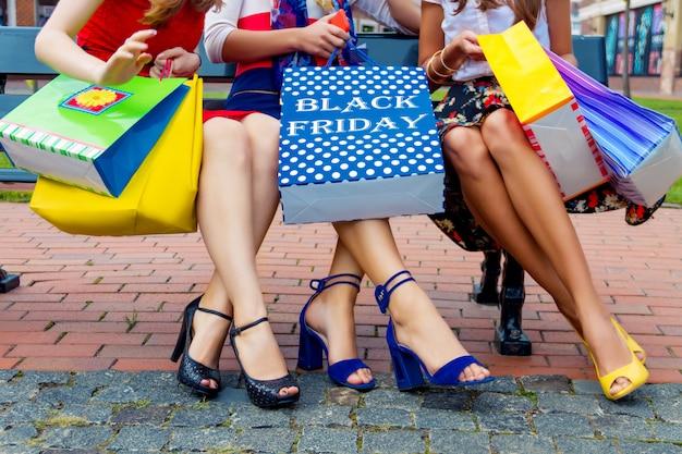 Pernas felizes dos amigos de meninas dos adultos das fêmeas das mulheres coloridas nos vestidos coloridos que sentam-se ao ar livre após ter feito compras no shopping com pacotes dos bens da loja.