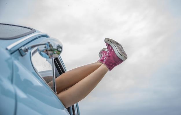 Pernas femininas através de um carro de janela
