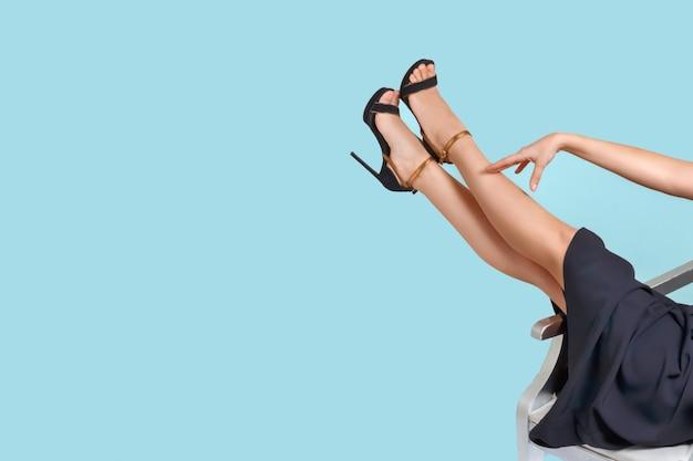 Pernas femininas bem arrumadas em sandálias de salto alto. pedicure, depilação, tratamento de varizes.