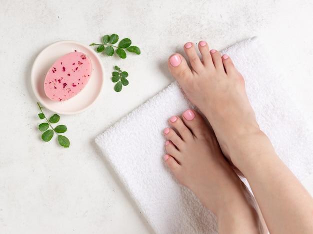 Pernas femininas bem cuidadas com uma delicada pedicure rosa