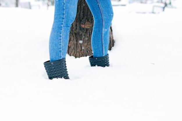 Pernas femininas cobertas de neve até os joelhos.