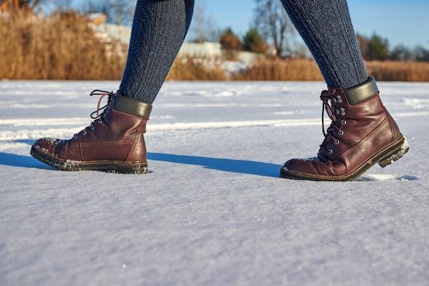 Pernas femininas com botas impermeáveis de couro marrom está caminhando para o inverno na neve fresca. moda casual, calçados da moda.