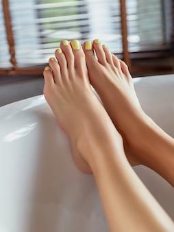 Pernas femininas com desenho de unhas amarelas no banheiro com luz do sol