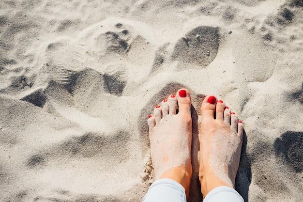 Pernas femininas com os pés descalços na areia da praia, vista superior