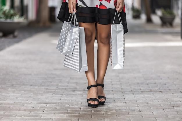Pernas femininas com sacos de compras nas mãos na cidade