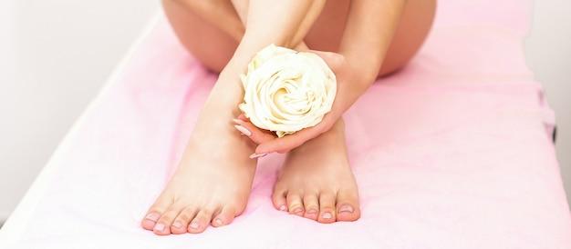 Pernas femininas com uma rosa branca em mãos femininas, sentadas em um sofá em um spa de beleza