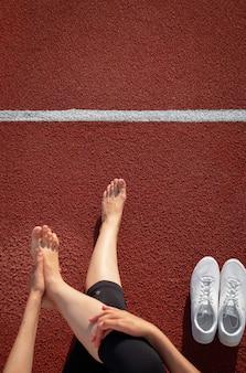 Pernas femininas de banner. a mão de uma mulher amarrando o cadarço do tênis no estádio. preparando-se para correr. espaço para texto. vista do topo. vertical