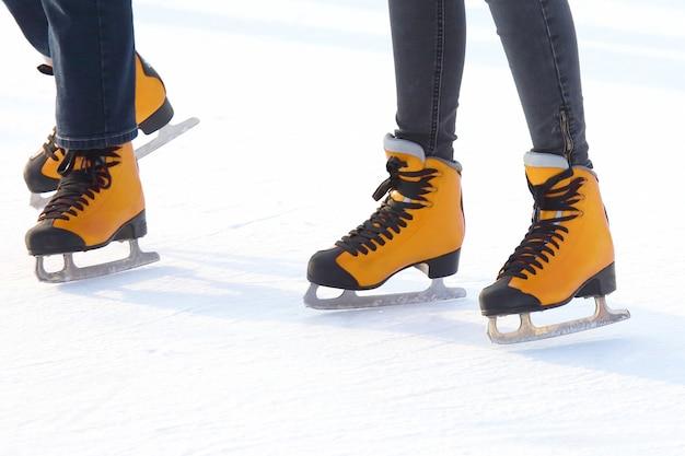 Pernas femininas de patins em uma pista de gelo. esporte e entretenimento. descanso e férias de inverno.