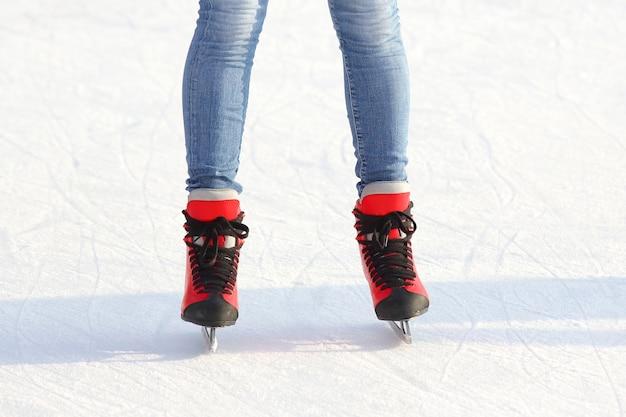 Pernas femininas de patins em uma pista de gelo