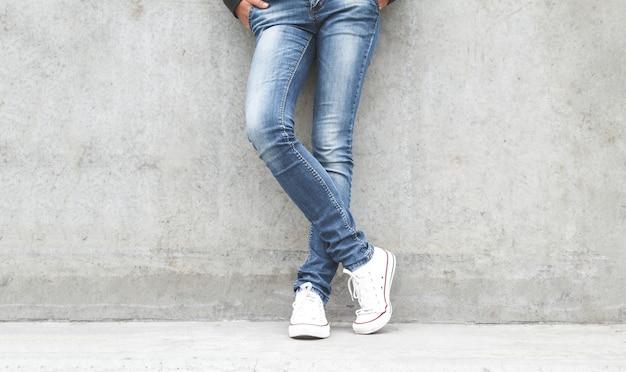 Pernas femininas de tênis e jeans perto de uma parede de concreto